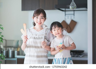 Asian young mom and daughter challenge cooking with kitchen tools