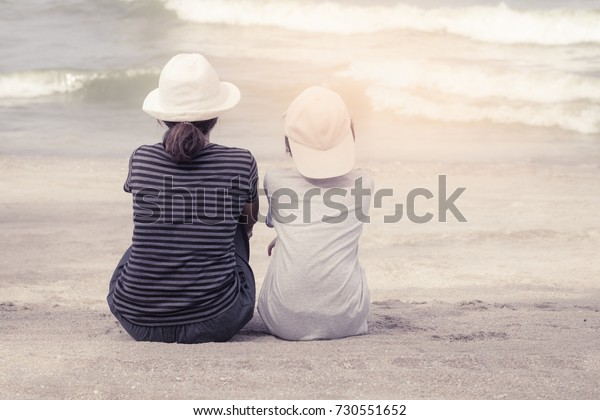 Asian young mother with daughter sitting on the beach during the summer holidays with vintage color tone