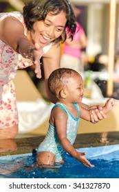 Asian Young  Mother Encourage Toddler Having Fun at Swimming Pool