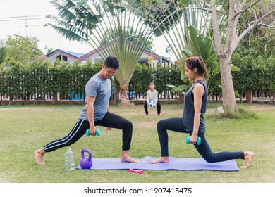 Asian young mother, father and child daughter doing exercising together with dumbbells is fun outdoors in nature a field garden park. Happy family kid sport and exercises for healthy lifestyle
