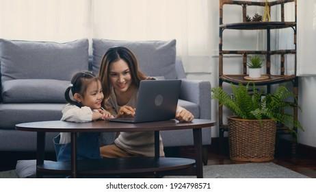 Asiatische junge Mutter mit Laptop-Computer, die ihren Kindern beibringt, im Wohnzimmer zu Hause online zu lernen oder zu studieren, Mutter und kleine vorschulische Tochter, die online am Computer lernt, Familienunterricht online