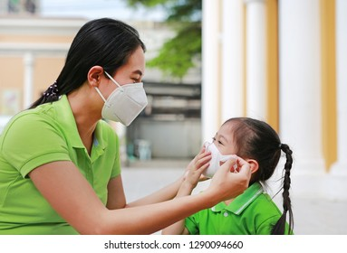 Asian young mother wearing protective mask for her daughter while outside.