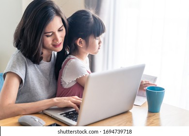 Asian young mother work from home. Woman use laptop for meeting with colleague while daughter sit on the lap and play. Mom happy to do job while taking care family. Covid-19, Social distancing concept