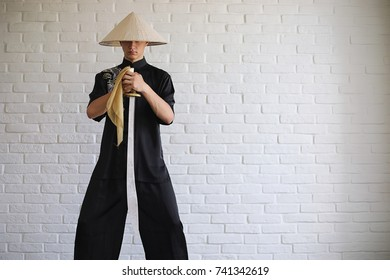 Asian young novice on a white brick wall background. A Vietnamese warrior with a sword hat wearing a kimono in black. Asian hero in robes and arms