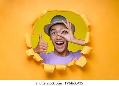 Asian Young optimistic man with excited expression, poses through torn paper hole, eye looking through fingers with happy face, showing thumb up with positive emotion