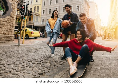 Asian young people in the city with skateboard and basketball. Woman being pushed by man  on skateboard outdoors on street, with their friends walking by in the city street.