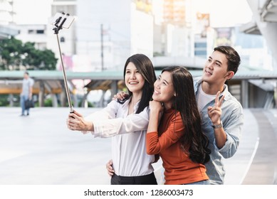 Asian young people of group best friends using smartphone selfie take photo with stick outdoors, Vocation and travel concept, Social media, Vintage tone.