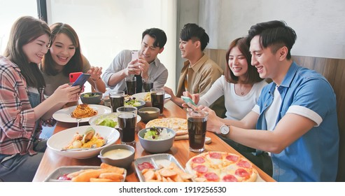 asian young people share their photos or fun video on smartphone with friends together happily in restaurant