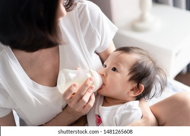 Asian young pretty mother giving bottle of her breast milk to cute baby sitting on her legs in bedroom at home. She holding the the bottle of mother milk and looking at the kid, eyes contact together.