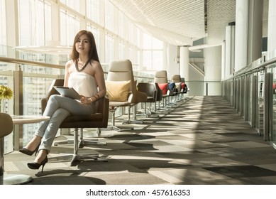 Asian young smile business woman working with tablet,  blurry and soft focus, has fair lighting, background has city sky, portrait woman