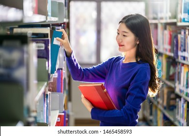 Asian young Student in casual suit searching the book from book shelf in library of university or colleage with various book background, Back to school concept