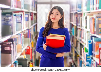 Asian young Student in casual suit holding after searching the book from book shelf in library of university or colleage with various book background, Back to school concept