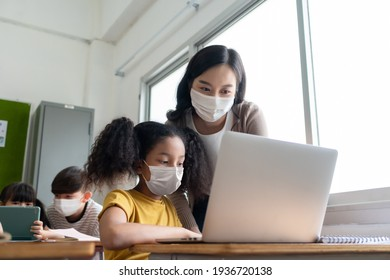 Asian Young Teacher with African American girl in protective face masks studying on laptop in classroom. Woman teaching diversity students in international school. Education and Learning on technology