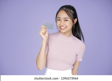 Asian young teenage beautiful cheerful girl hold membership or credit card in pink shirt, on violet background