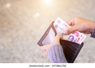 Asian young  tourist counting or checking banknote in black wallet at the airport. Budget for traveling concept