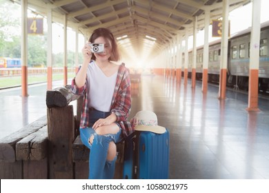 Asian young traveler woman with luggage looking at the camera while waiting train on railway platform