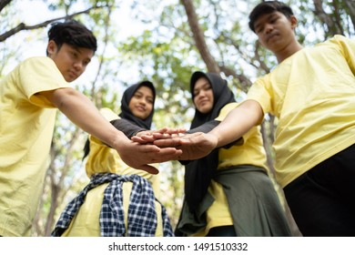 Asian young of volunteers hands together in park
