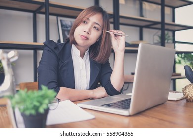 Asian Young woman accountant having trouble with laptop.Young woman is thinking about the upcoming holiday.