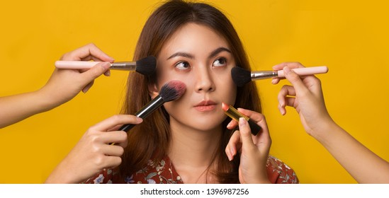 Asian young woman applying makeup in studio yellow background, Makeup artist makeover on her face.