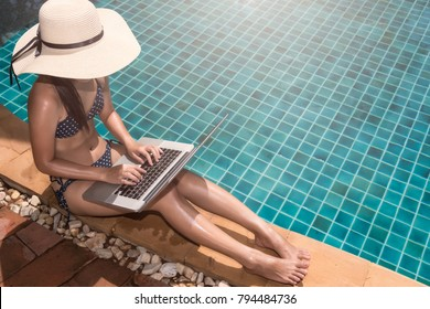 Asian Young woman in big hat relaxing on poolside with laptop computer blue water