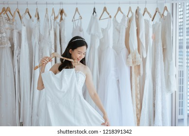 Asian young woman bride trying on wedding dress at modern wedding,Happy and smiling