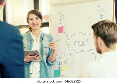 Asian young woman business officer explaining idea internal meeting to her project team in modern office. They are the multi ethnic business person group in casual suit. Project and Business concept.