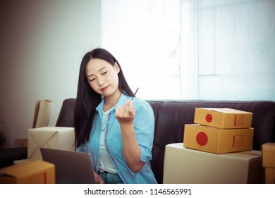 Asian young woman business work at home holding credit card and using laptop smart phone for online shopping and sale.small and medium enterprise business ,sale online concept,happy to sale