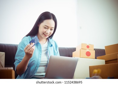 Asian young woman business work at home holding credit card and using laptop for online shopping and sale.small and medium enterprise business ,sale online concept.