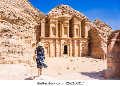 Asian young woman in colorful dress and hat enjoying at The Monastery, Petra's largest monument, UNESCO World Heritage Site, Jordan.