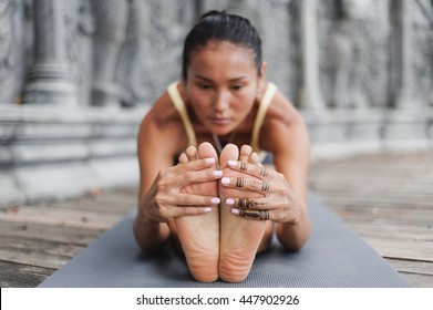 Asian young woman doing yoga in abandoned temple. Selective focus. Blurred background
