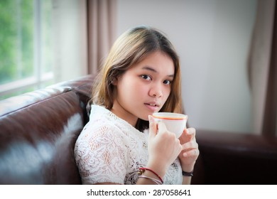 Asian young woman drinking coffee at home