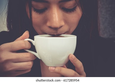 Asian young woman are drinking cup of coffee, vintage style.