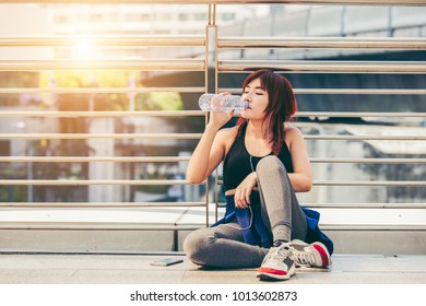 Asian young woman drinking water after exercise, Beautiful fitness,woman drinking water after work out exercising