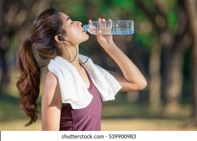 Asian young woman drinking water after jogging