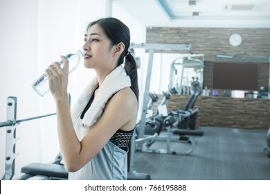 Asian young woman drinking water after exercise in sport club, asian athlete drinking a plastic bottle of water at the gym. Sport and health care concept