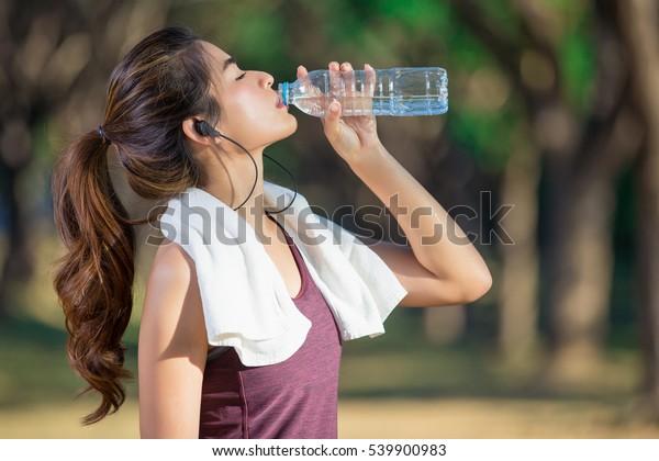 ジョギング後に水を飲むアジアの若い女性