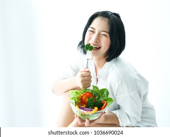 Asian young woman eatiing salad on white background diet food concept