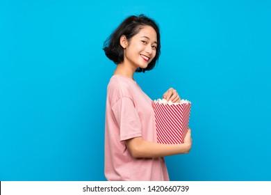 Asian young woman eating popcorns