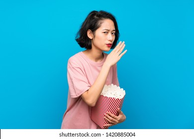 Asian young woman eating popcorns whispering something