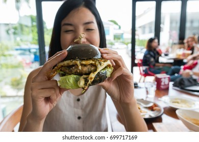 an asian young woman enjoy eating a black hamburger in the restaurant