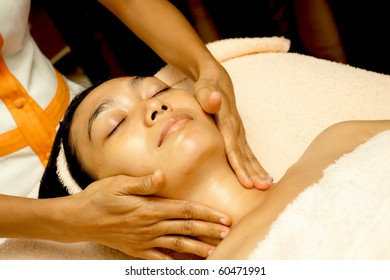 Asian young woman face massage in facial treatment