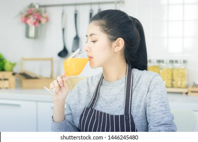 Asian young woman with glass of orange juice sitting at kitchen table,Health food concept