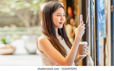 Asian young woman hand using smart mobile phone scanning the movie tickets machine for buy and get the coupon in department store,lifestyle and leisure,entertain and technology scanner concept