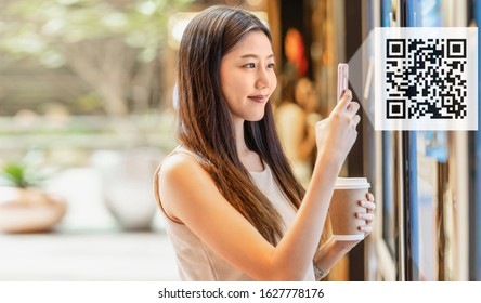 Asian young woman hand using smart mobile phone scanning bar code and QR code to movie tickets machine for buy and get the coupon in department store,lifestyle and leisure, technology scanner concept