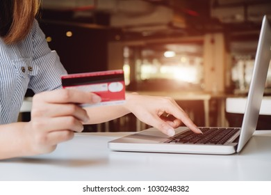 asian young woman hands holding credit card and using laptop smart phone Online shopping.Online shopping concept