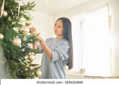 Asian young woman hanging Christmas balls on Christmas tree and preparing for holiday