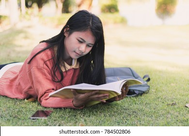 Asian young woman happiness relax reading with book on the grass, space for text
