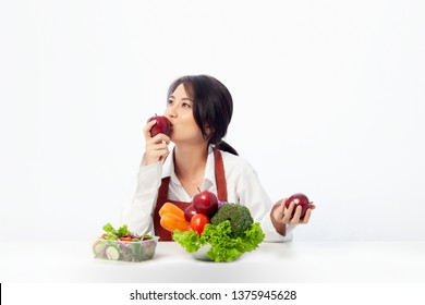 Asian young woman is happy holding and kissing fresh fruit apple with vegetables,  Healthy, Fresh food, Clean eating recipes to fuel body from the inside out concept.