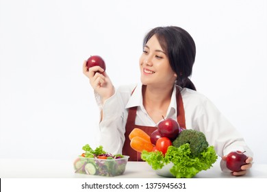 Asian young woman is happy holding fresh fruit apple with vegetables,  Healthy, Fresh food, Clean eating recipes to fuel body from the inside out concept.