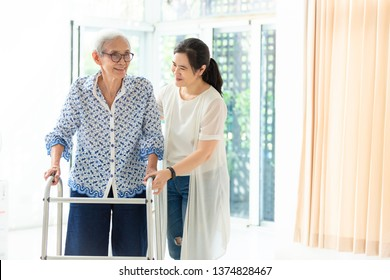 Asian young woman helping senior woman in using walker during rehabilitation, close up of carer supporting her elderly grandmother with walking and exercising at home